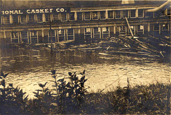 Flood damage and piled lumber, French Broad River,  July 1916. D.H. Ramsey Library Special Collections, University of North Carolina at Asheville