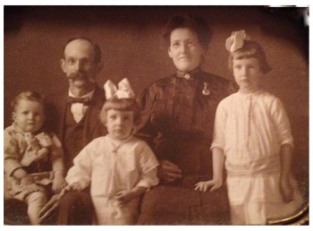 Asbury, Ella, and their children, ca. 1918. Nurse's watch on LH side of dress.