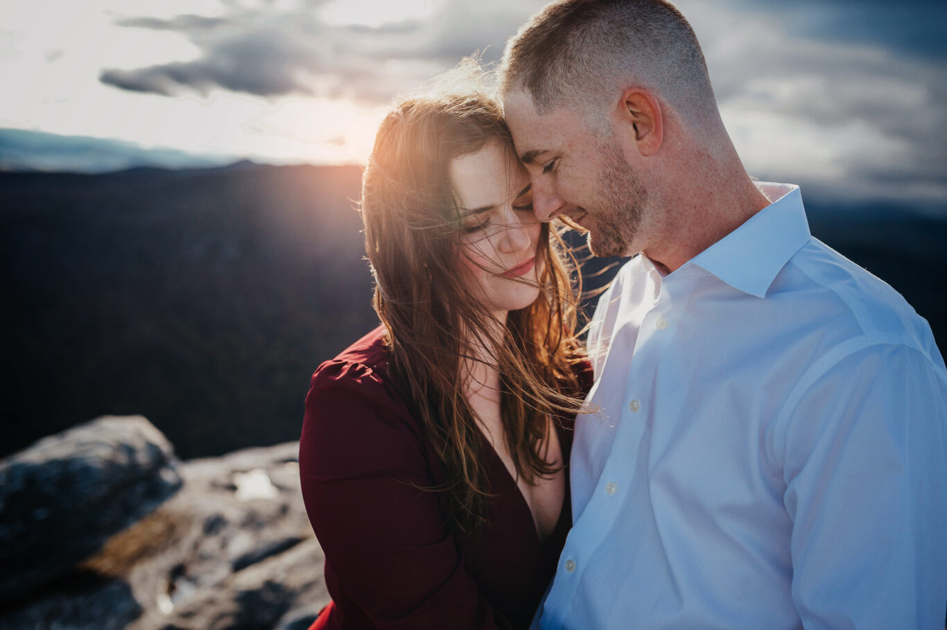 Engaged Couple embraces on a mountain top in Asheville, NC.