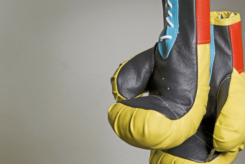 yello worn out boxing gloves hanging up