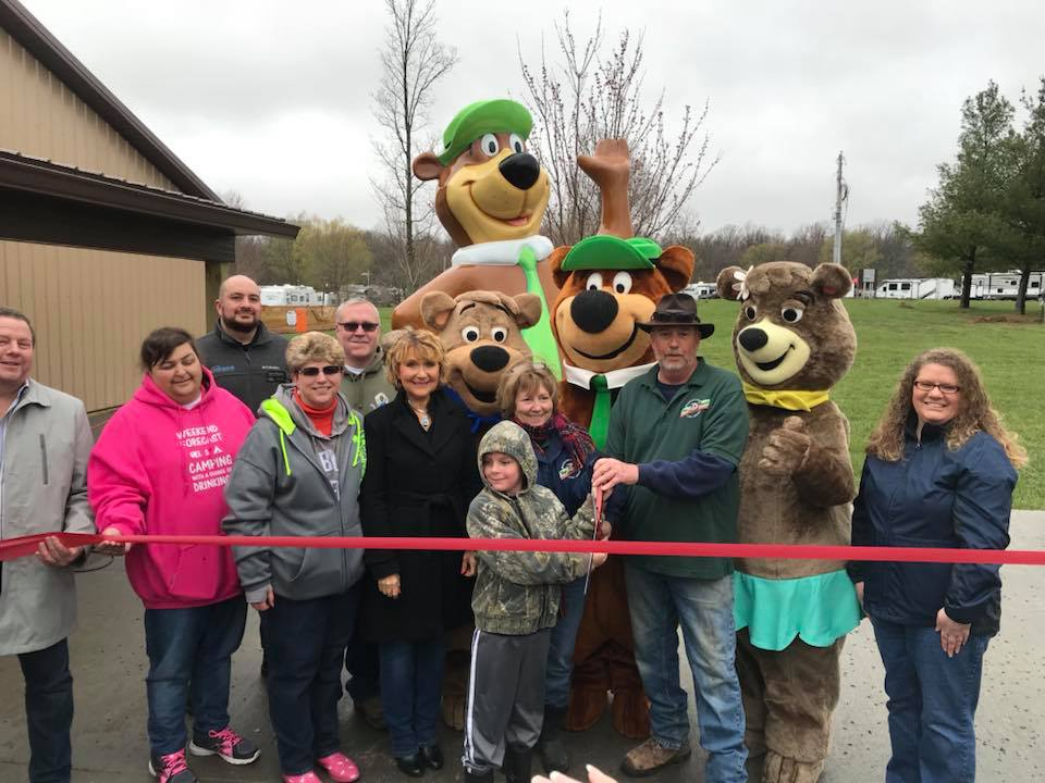 owners of jellystone park cutting ribbon in front of yogi bear statue