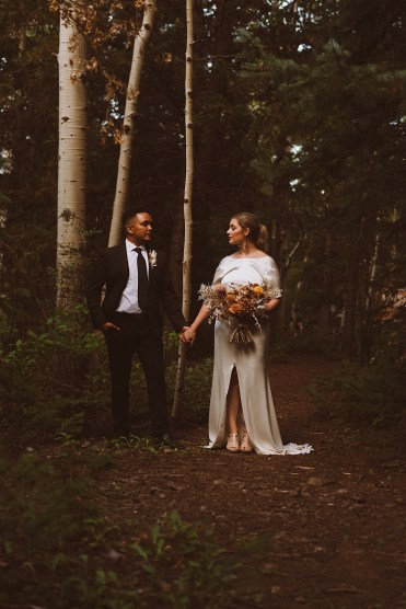 Bride and groom standing in the forest together holding hands in Colorado | Wedding portraits | Elopement portraits | Bride and groom elopement photos | Elopement wedding photos in Colorado | Colorado wedding photos | Colorado elopement photos | Elopement at Treehaus, Colorado | Treehaus Colorado | Colorado elopement | Treehaus elopement | Colorado elopement venue | Colorado mountain elopement venue | Unique elopement venue | Elopement venue in Colorado | Ashley Joyce Photography 2020