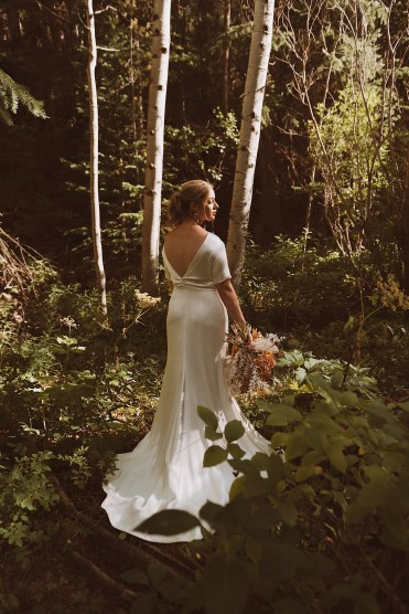 Bride standing in the woods of Colorado at Treehaus Colorado | Wedding portraits | Elopement portraits | Bride and groom elopement photos | Elopement wedding photos in Colorado | Colorado wedding photos | Colorado elopement photos | Elopement at Treehaus, Colorado |  Treehaus Colorado | Colorado elopement | Treehaus elopement | Colorado elopement venue | Colorado mountain elopement venue | Unique elopement venue | Elopement venue in Colorado | Ashley Joyce Photography 2020