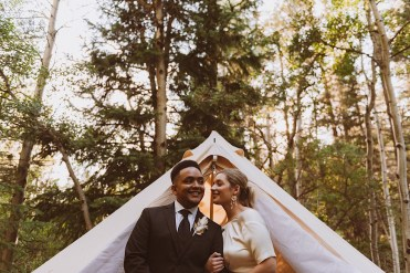 Bride and groom laughing together in front of wedding tent at Treehaus Colorado | Wedding portraits | Elopement portraits | Bride and groom elopement photos | Elopement wedding photos in Colorado | Colorado wedding photos | Colorado elopement photos | Elopement at Treehaus, Colorado |  Treehaus Colorado | Colorado elopement | Treehaus elopement | Colorado elopement venue | Colorado mountain elopement venue | Unique elopement venue | Elopement venue in Colorado | Ashley Joyce Photography 2020