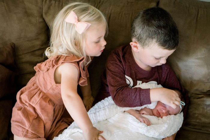 Big brother and sister hold newborn for an in-home family photo session.
