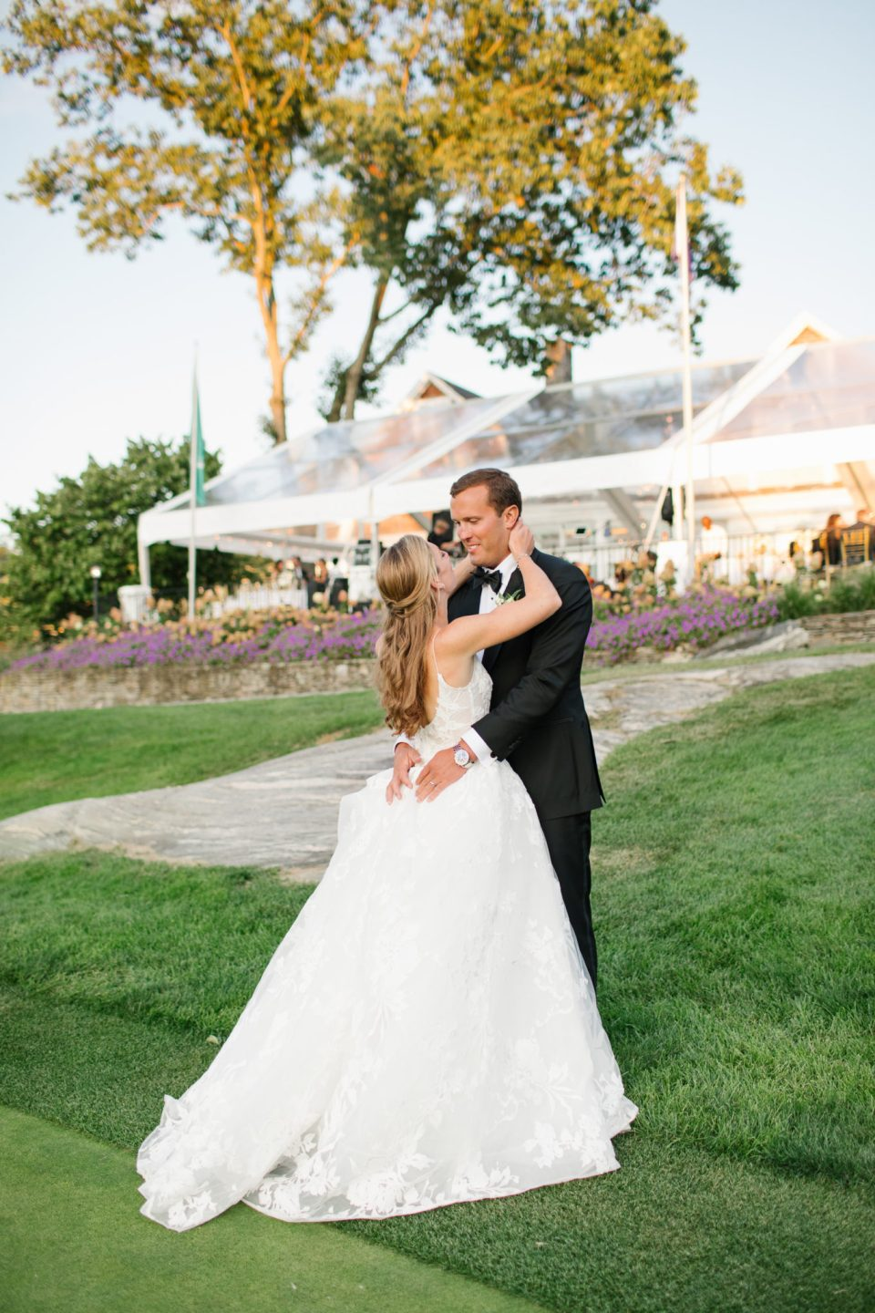 tented wedding reception behind bride and groom photographed by Ashley Mac Photographs
