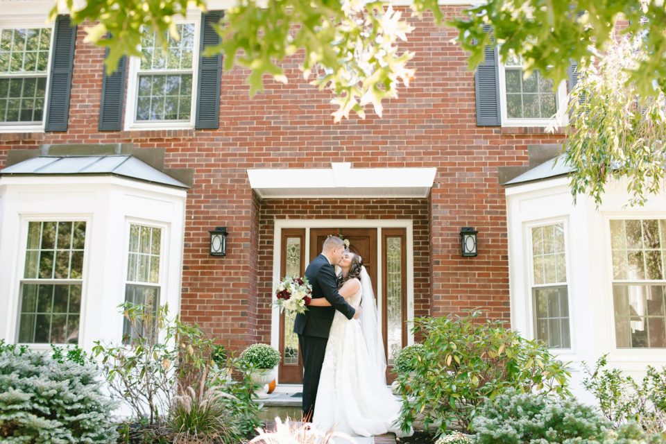 bride and groom embrace on wedding day with Ashley Mac Photographs