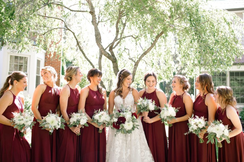 bridesmaids with burgundy gowns and ivory florals photographed by Ashley Mac Photographs