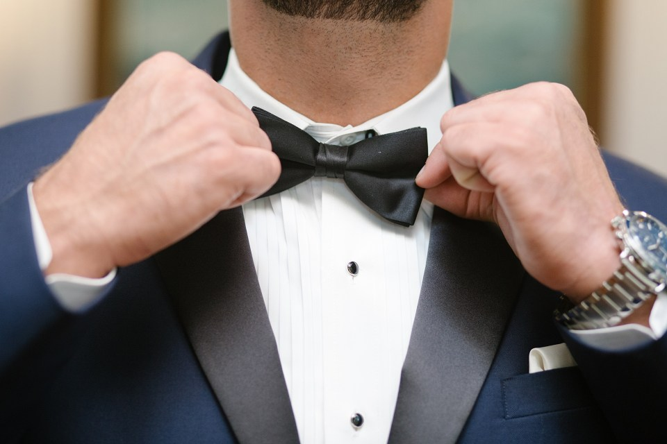 groom adjusts tie with navy tux photographed by Ashley Mac Photographs