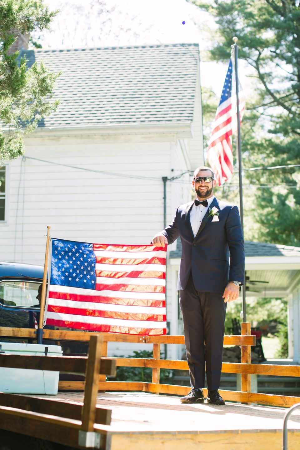groom holds American flag before wedding day