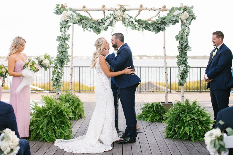 wedding ceremony at Rumson Country Club Riverhouse with floral arch photographed by Ashley Mac Photographs