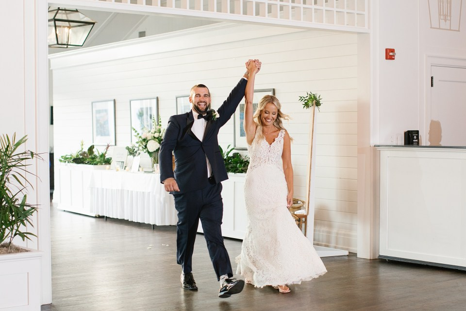 bride and groom enter reception at Rumson Country Club Riverhouse with Ashley Mac Photographs