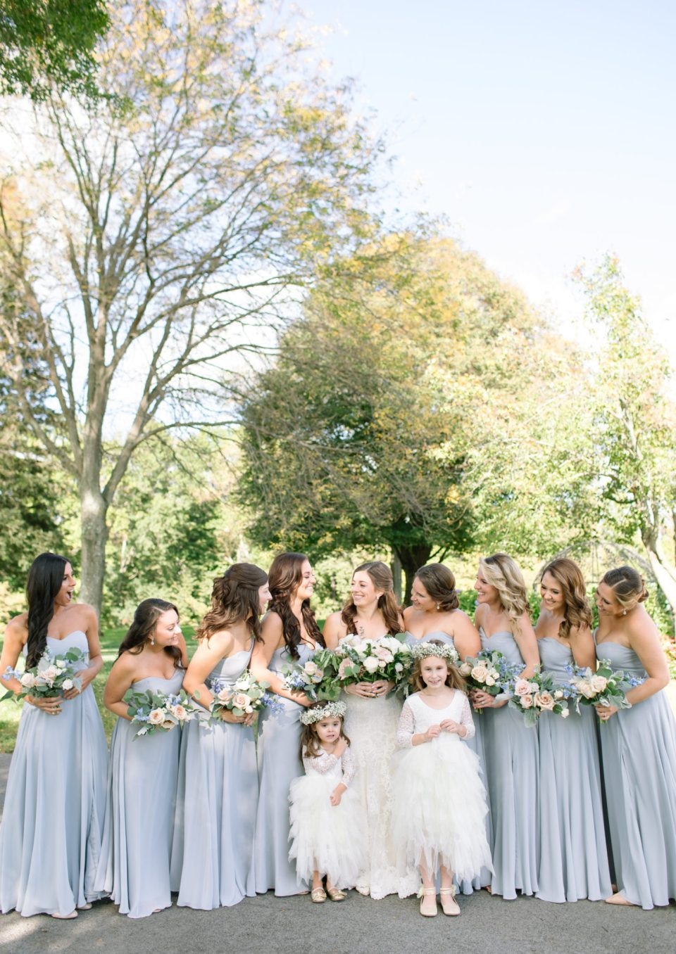 bride with bridesmdaids in dusty blue dresses photographed by Ashley Mac Photographs
