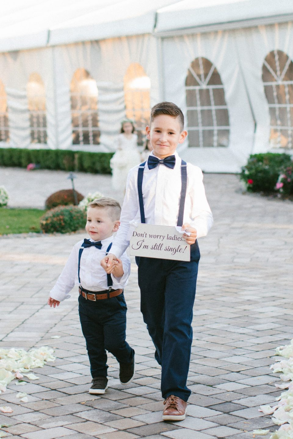 ring bearers walk down the aisle at West Hills Country Club