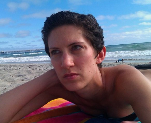 Girl with short dark hair laying on beach contemplating life