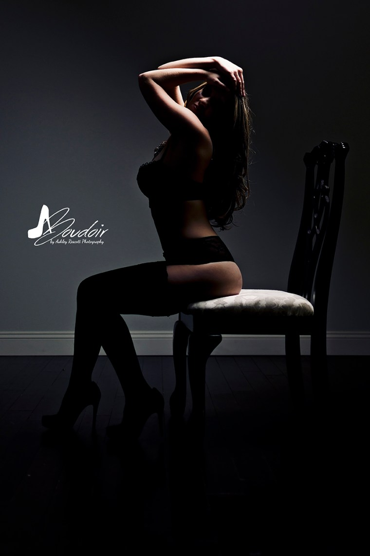 Woman sitting on chair with high contrast lighting