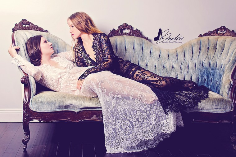 two women reclining on couch in lace dresses