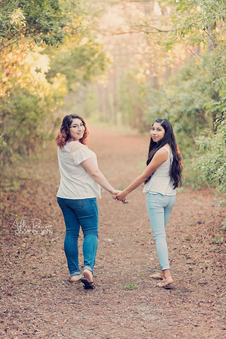 sisters walking in woods holding hands