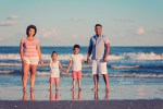 family standing in ocean at beach