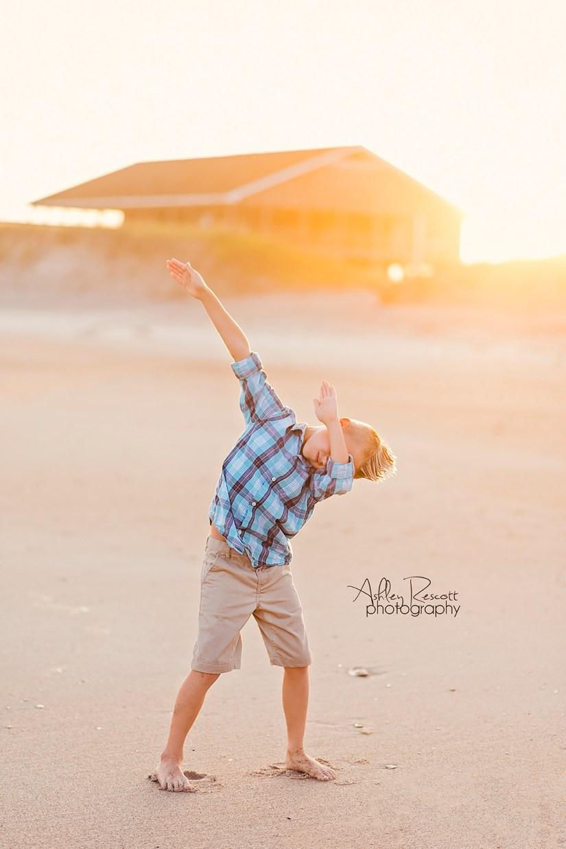 boy dabbing on beach at sunset