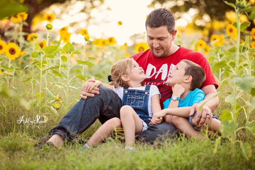 Dad with kids in sunflower field