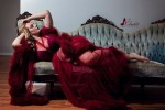 Woman in sheer red feathered robe lounging on blue victorian couch during her boudoir session