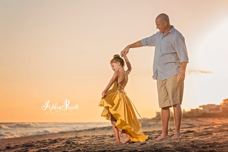 Dad dancing with daughter in a yellow dress on the beach at sunset