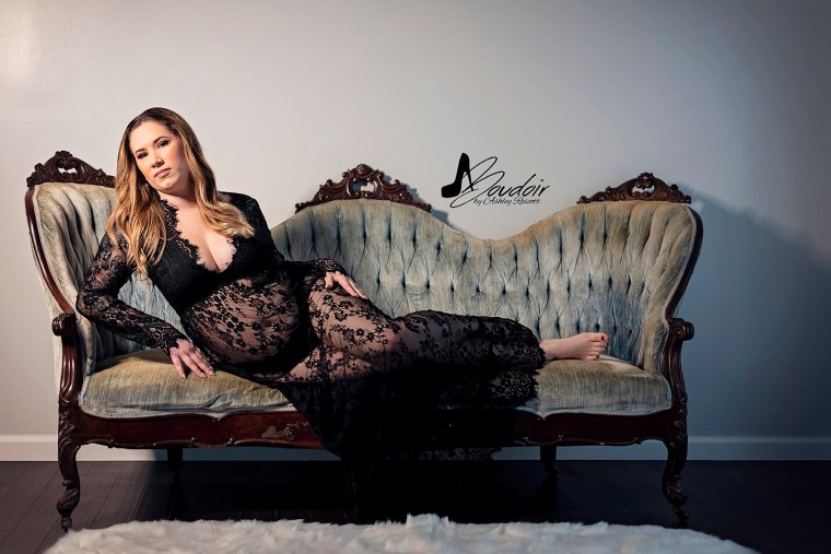 woman in black lace dress lounging on blue victorian couch