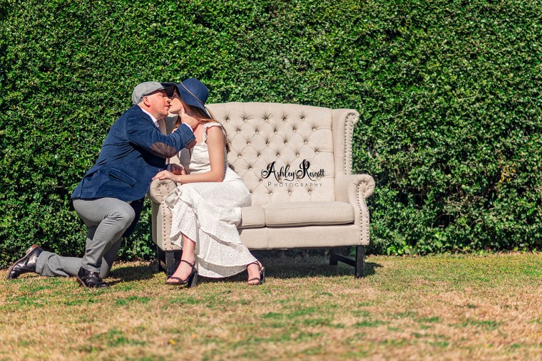 man on one knee kissing his fiancee in front of a tall hedge
