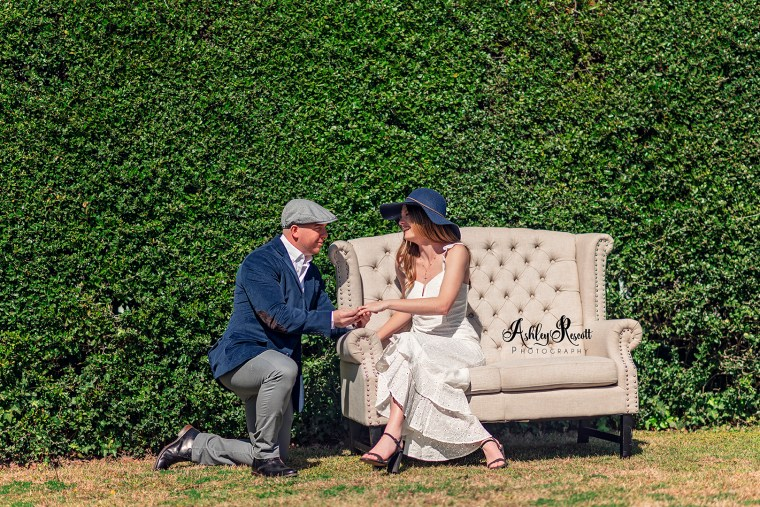 man proposing while she sits on a couch in front of a hedge