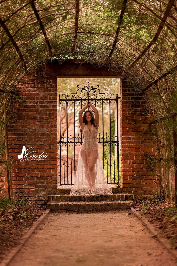 woman standing in front of gate in dress