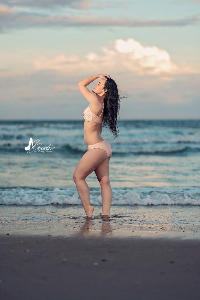 woman in bikini standing in water at beach