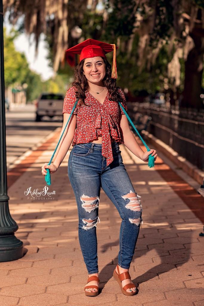 high school senior girl standing on sidewalk, grad cap & tassels
