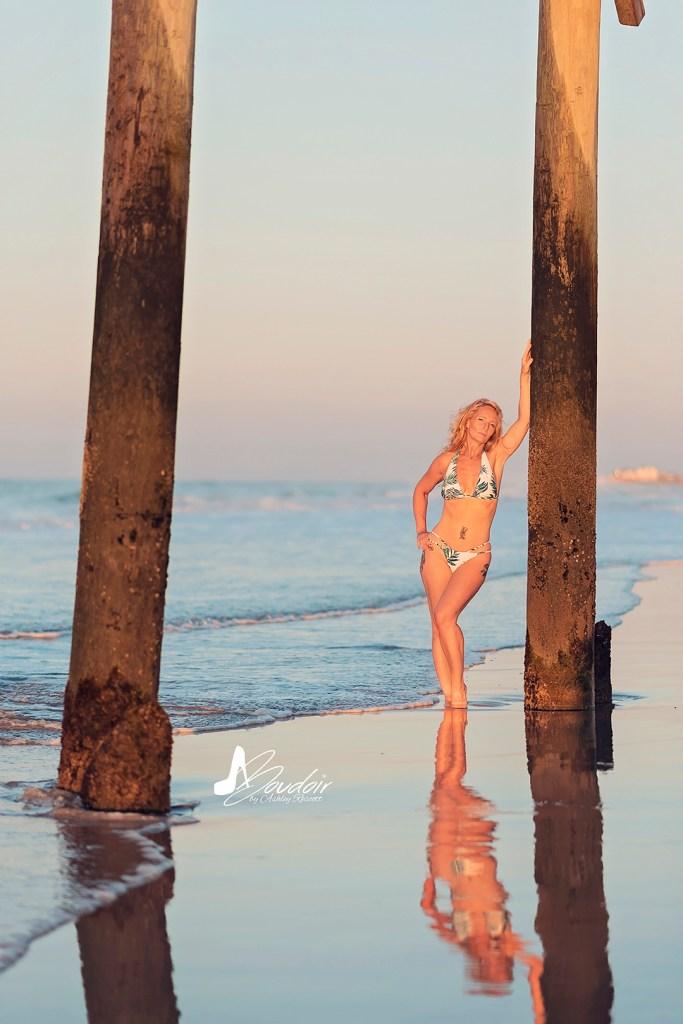 woman leaning against pillar on beach
