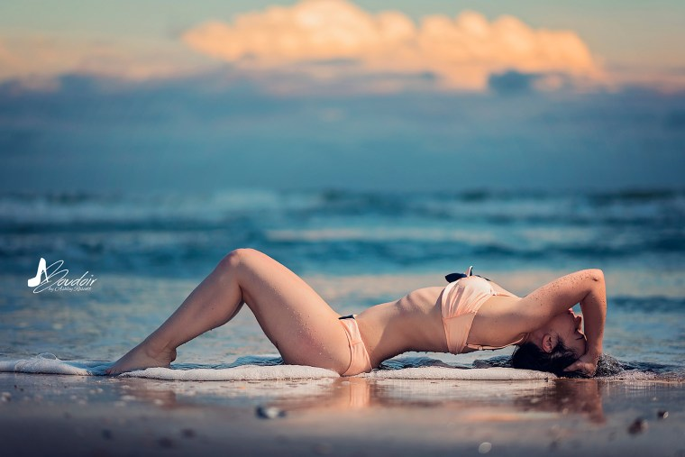 woman lying in front of water on beach