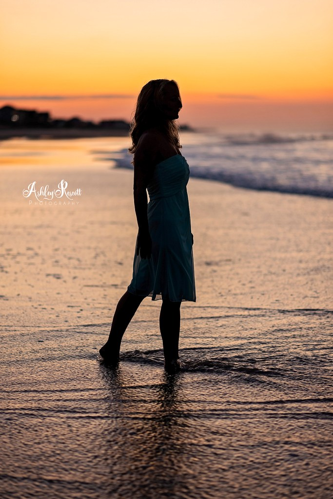 silhouette of woman walking toward water