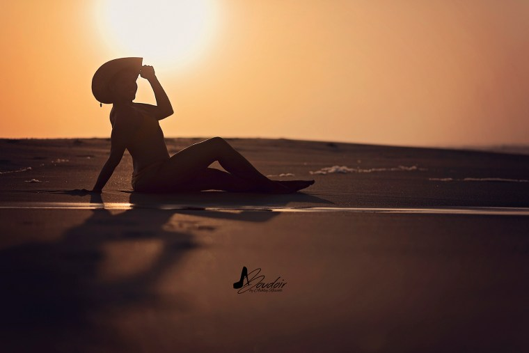 silhouette of woman sitting on beach at sunrise