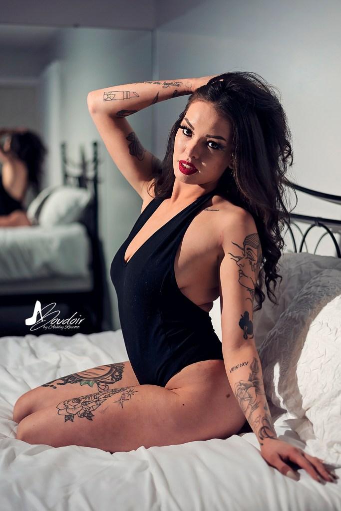 woman kneeling on bed in bodysuit