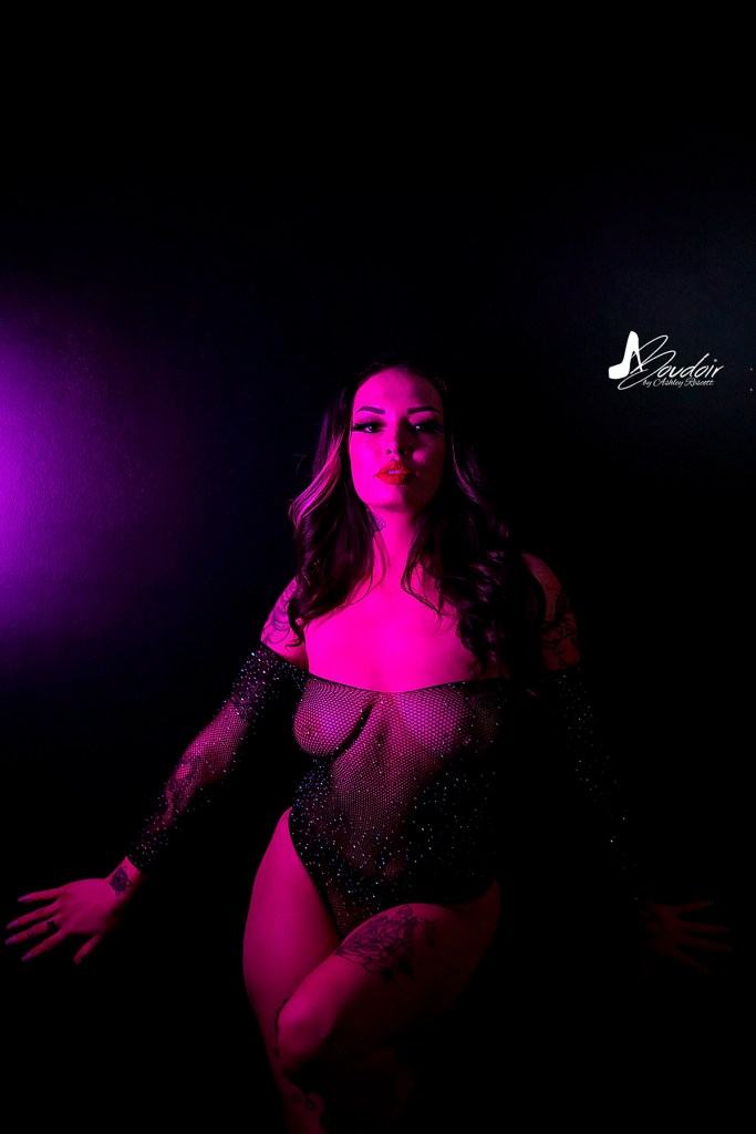 woman standing against wall with magenta light