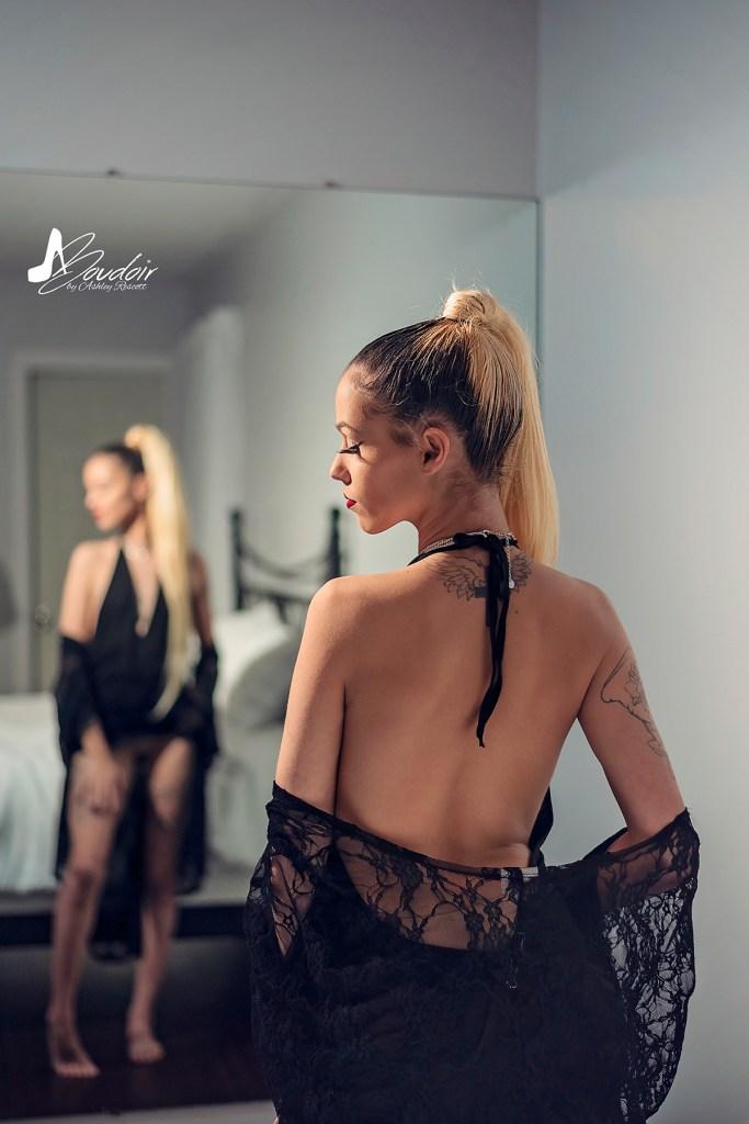 boudoir model standing near bed, taking off kimono, looking down