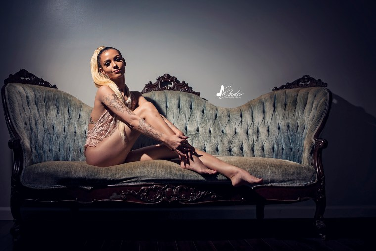 boudoir model sitting on couch with arms wrapped around legs