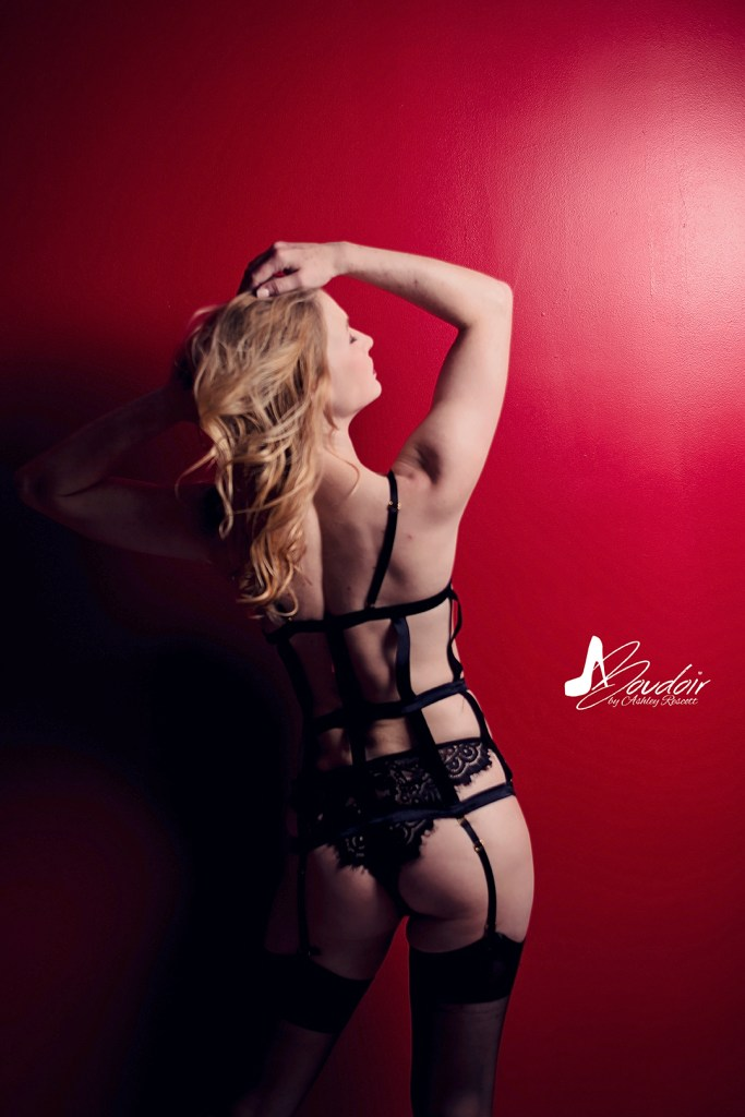 woman in black lingerie standing at red wall