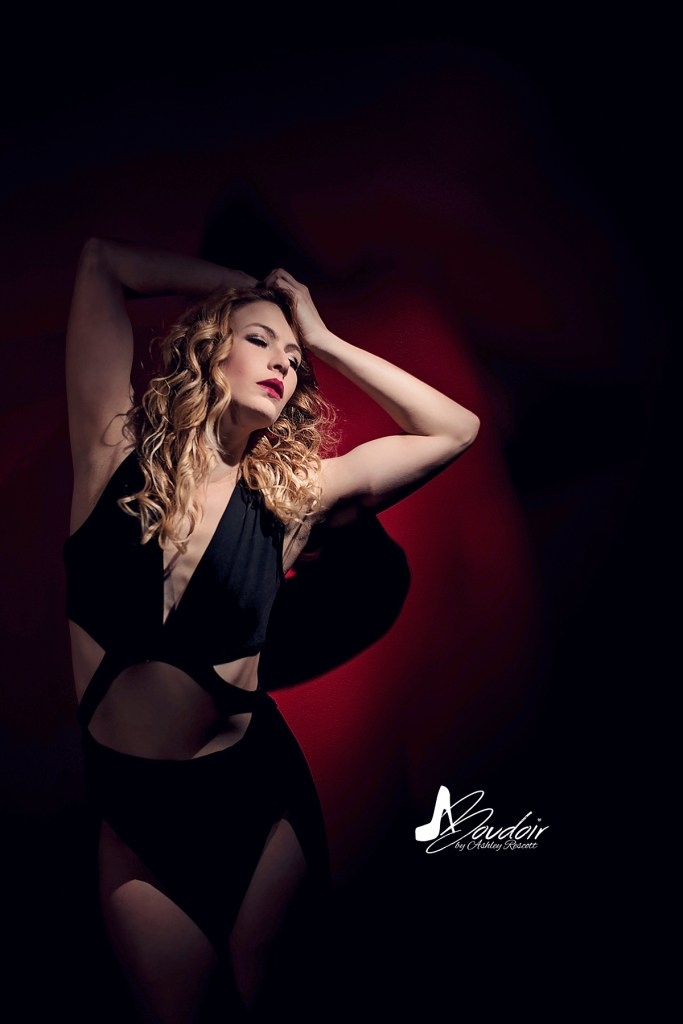 Blonde model in black dress on red wall with spotlight
