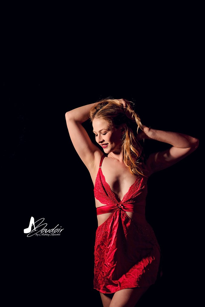 blonde boudoir model in red dress in front of black wall