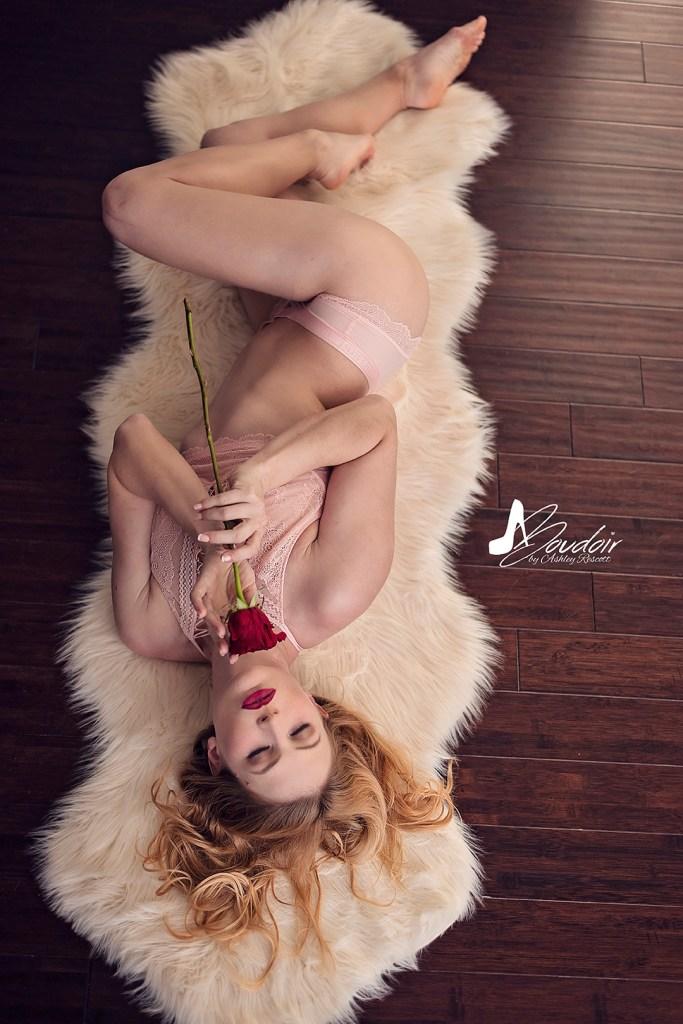 woman lying on sheepskin rug smelling a rose