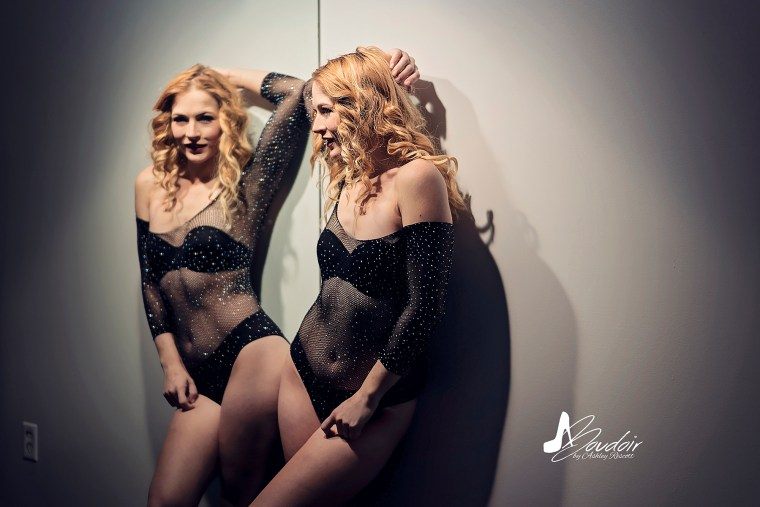 model by mirror while wearing lingerie, dramatic boudoir lighting