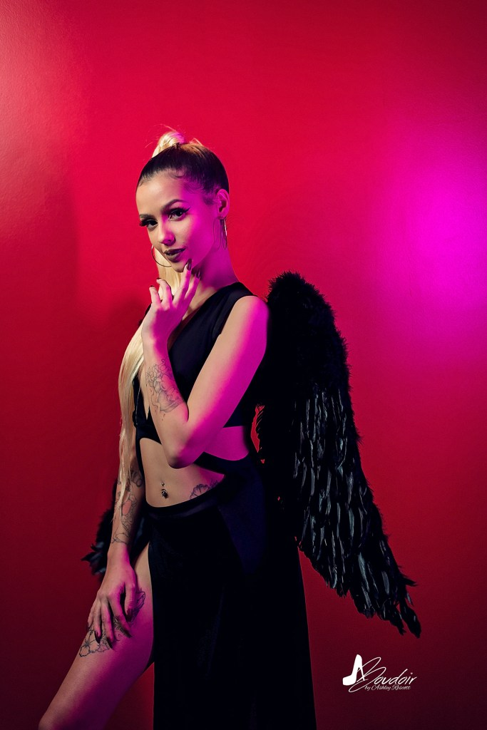 smirking dark angel in pink light