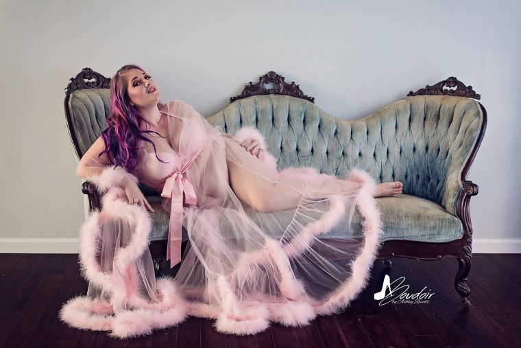 boudoir client lounging on couch in feathered robe