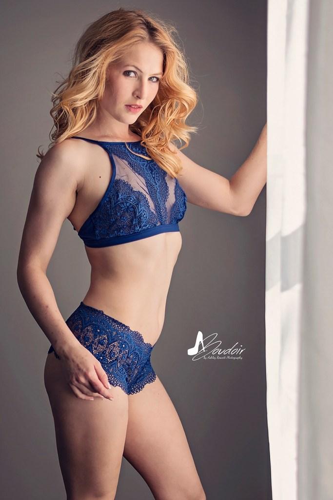 woman in blue lingerie standing by window