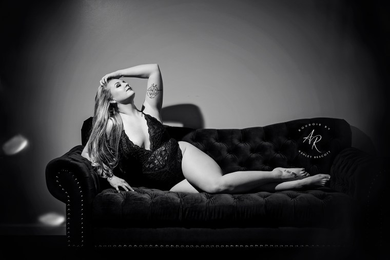 black and white boudoir portrait of woman lounging across couch